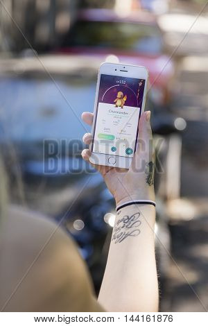 Gothenburg, Sweden - August 14, 2016: Tattooed woman holding a smartphone while playing Pokemon Go, a free-to-play location based augmented reality mobile game developed by Niantic for iOS and Android devices.