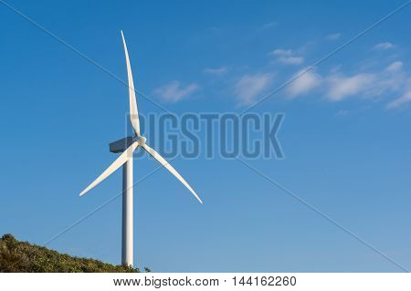 Wind turbine on a green hill generating electricity