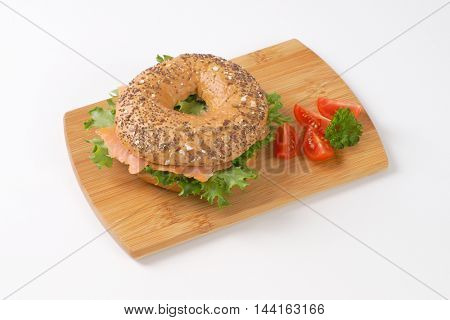 bagel sandwich with smoked salmon on wooden cutting board