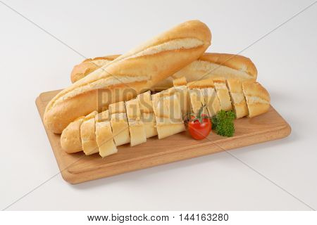 whole and sliced french baguettes on wooden cutting board