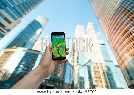 Russia, Moscow - August 24: 2016 Smartphone with Pokemon Go application. On the background of skyscrapers. Augmented reality mobile game developed by Niantic for Smartphone