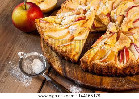 Traditional apple pie on a wooden table, with apple and powdered sugar