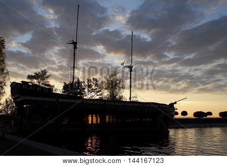 Old masted wooden ship moored in the sea bay at sunrise stock photos