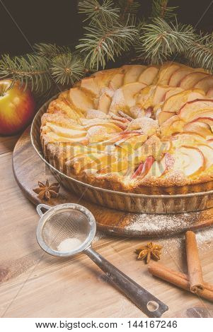 Traditional apple pie on a wooden table, with apple and powdered sugar. Near the Christmas tree branches, toned