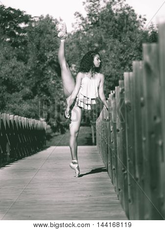 Latin dancer with leg raised above his head on the bridge of a park Monochrome