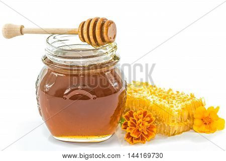 Jar full of honey next to the honeycomb and flowers on white background