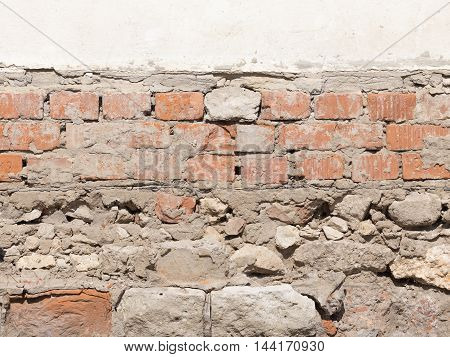 uneven surface of old wall painted bright white streaks with oil paints and old bricks underneath fastened rough gray cement