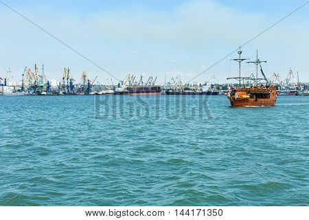 Sailing ship with lowered sails departs from the coast on the background of the commercial port