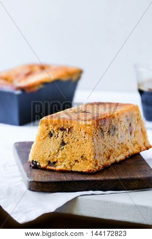 Orange chocolate chip loaf cake. Dark wooden board and white cloth. Light food photography.