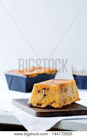 Orange chocolate chip loaf cake. Dark wooden board. White background. Free text space. Light food photography.