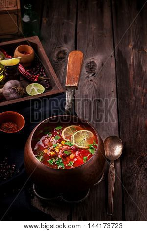 Tomatoe Mexican Soup With Spices And Lime On Wooden Table