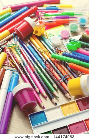 Full background of a colorful assortment of school supplies vintage toned