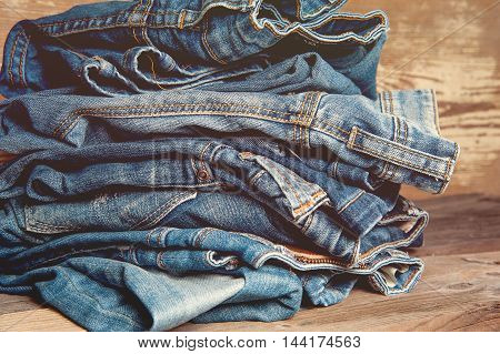 Pile of Old Indigo Jeans Denim on Wooden Table Background Texture Toned