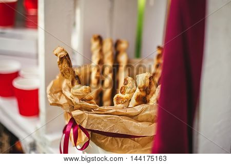 Tasty breadsticks in paper basket. Food on wooden background