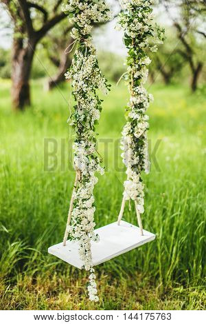 White wooden swing with flowers in garden