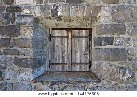 weathered old wooden door in stone wall