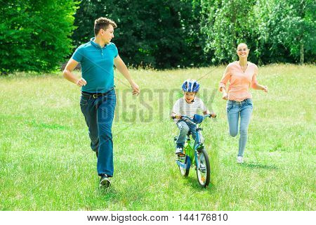 Happy Parents Running With Their Son Riding A Bicycle In The Park