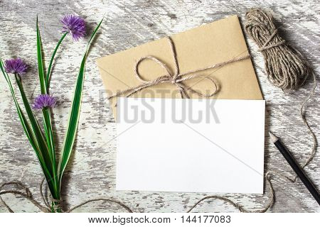Blank white greeting card and envelope with purple wildflowers and pencil on white rustic wood background for creative work design