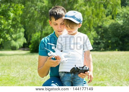 Father And Son Playing With The White Drone In The Park