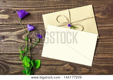 bouquet of purple wildflowers with blank white greeting card and envelope with copy space on rustic wooden background