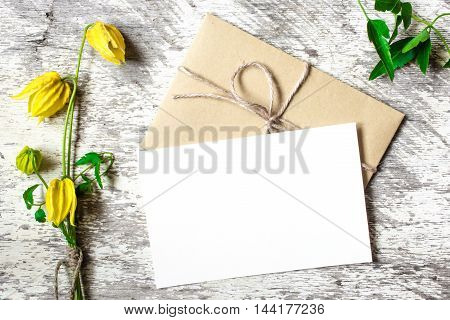 bouquet of yellow flowers with blank white greeting card and envelope with copy space on white wooden background