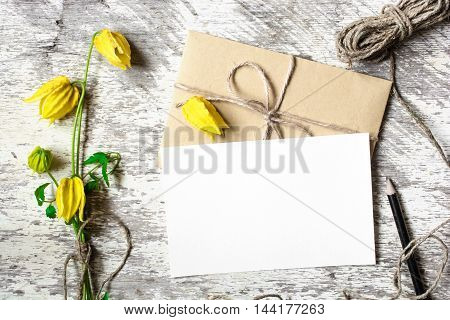 Blank white greeting card and envelope with yellow autumn flowers and pencil on white rustic wood background for creative work design