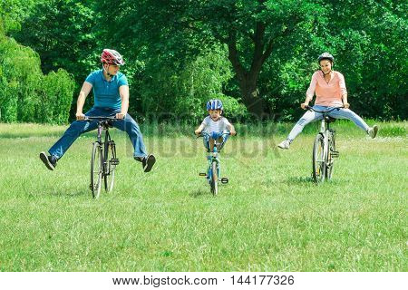 Happy Boy Enjoying Riding On Bicycle In The Park With His Parents