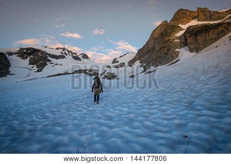 A mountain climber climbs over a glacier