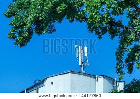 Cellular antenna located on the roof of the building on a background of sky framed by the branches of a tree