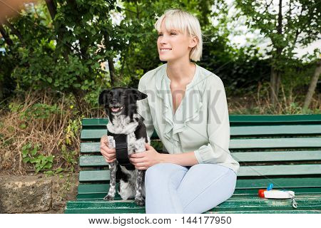 Young Happy Woman Sitting With Her Dog On The Bench