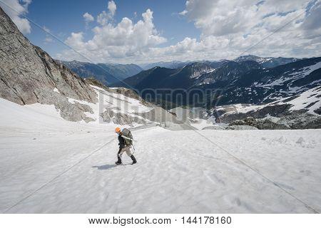 A mountain climber decends on a glacier