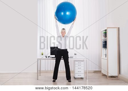Happy Businesswoman Stretching Her Arms Using Fitness Ball In Office