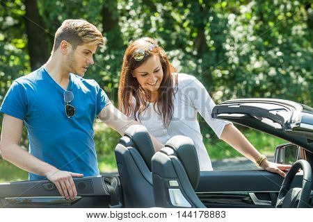 Smiling Young Couple Looking At Their Newly Purchased Car