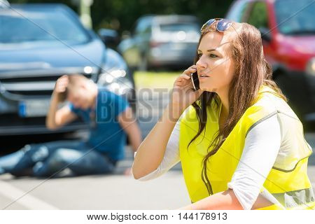 Woman Talking On Cellphone At Street After Car Accident