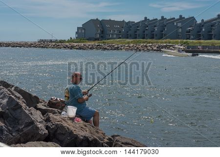 Fisherman's Cove Manasquan NJ USA -- August 25 2016 Man in Fisherman's Cove patiently fishing from the Rocks by the inlet. Editorial Use Only