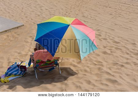 Anonymous holiday maker relaxes and reads under a colorful beach umbrella