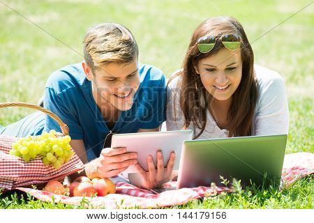Happy Couple Using Digital Tablet And Laptop While Lying In Park