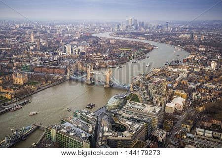 London England - Aerial Skyline view of London with the iconic Tower Bridge the Tower of London and skyscrapers of Canary Wharf on a cloudy afternoon