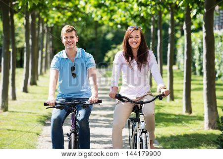 Portrait Of Smiling Young Couple Enjoying The Ride On Bicycle In Park