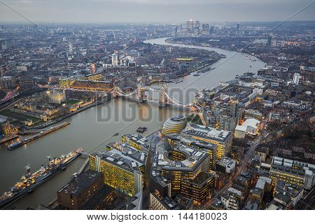 London England - Aerial Skyline view of London with the world famous Tower Bridge Tower of London and skyscrapers of Canary Wharf at dusk