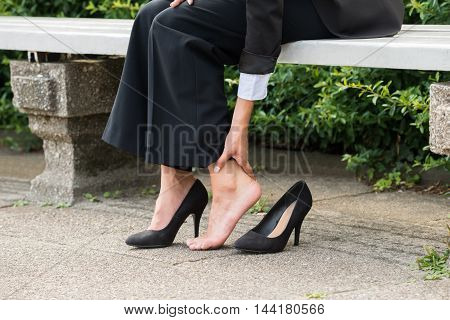 Close-up Of Businesswoman's Hand Sitting On Bench Removing High Heels