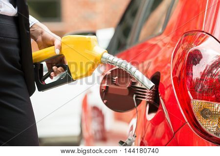 Close-up Of Businesswoman's Hand Refueling Car's Tank By Holding Petrol Pump Nozzle