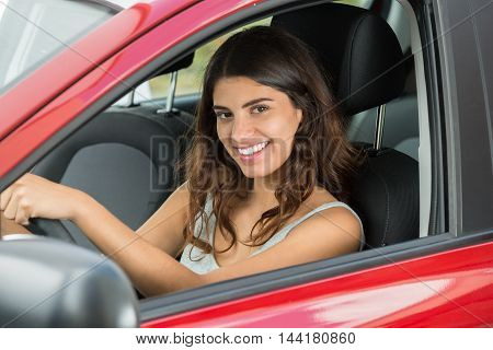Side View Of A Young Happy Woman Driving Car