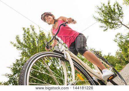 Low Angle View Of A Happy Young Female Cyclist Riding Bicycle
