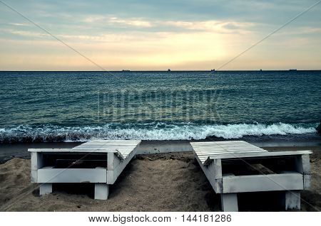 warm summer evening with sundeck chairs foamy waves and the bright sky on the Black Sea