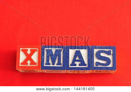 Xmas spelled with Alphabet blocks on a red background