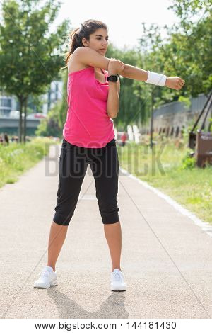 Sporty Young Woman Stretching Her Hands While Exercising In Park