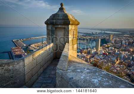 Small tower on the steep of Santa Barbara castle in sunlight, Alicante, summer Spain