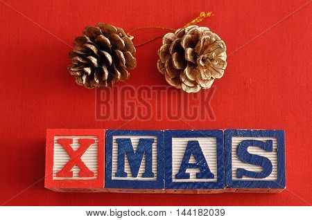 Xmas spelled with Alphabet blocks and acorn christmas tree decorations on a red background