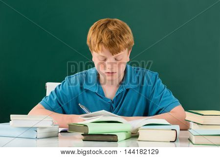 Boy In Classroom With Books On Desk Against Green Chalkboard
